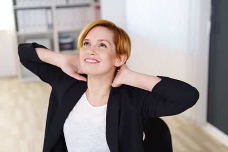 Happy satisfied young businesswoman relaxing stretching her back with her hands behind her head and looking upwards with a smile Stock Photo