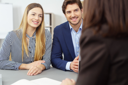 Young couple meeting with an investment broker sitting side by side smiling as they listen to what she has to say