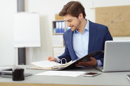 事務所の机に座って、フォルダー内の書類を探している文書を扱う青年実業家。コピー スペース