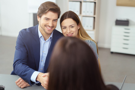 Adviser shaking hands with a young couple during a meeting or presentation with focus to the smiling husband