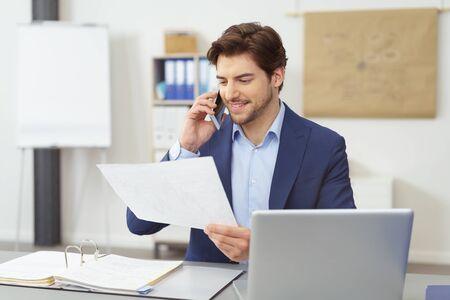 Junger Geschäftsmann, der ein Handdokument an einem Handy mit einem erfreuten Lächeln bespricht, während er an seinem Schreibtisch im Büro gesetzt wird