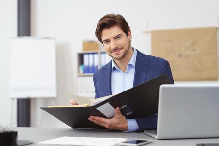 彼は書類を開いて office バインダーにホルダーを座っていると、カメラを見て優しい笑顔でハンサムな実業家