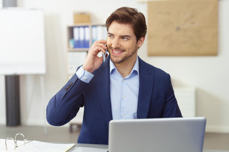 Young businessman without tie talking by mobile phone sitting in office behind laptop, looking away and smiling