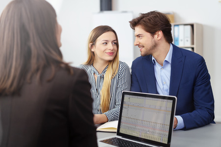financial planning married: Young married couple in a meeting with a broker or agent sitting looking at each other smiling as they reach a decision