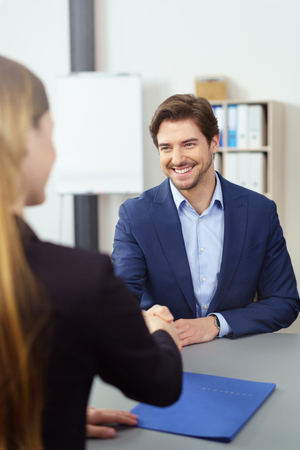 hand job: Businessman greeting a job applicant with a wide welcoming smile and shaking her hand, over the shoulder view Stock Photo