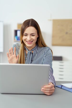 interacts: Happy smiling woman waving at her laptop computer as she interacts on a video conferencing call while sitting in an office Stock Photo