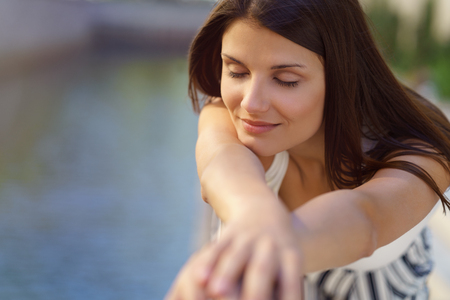 Pretty brunette woman enjoying a quiet moment as she rests her chin on her outstretched arms with her eyes closed and a smile of pleasure alongside a tranquil river Stock Photo