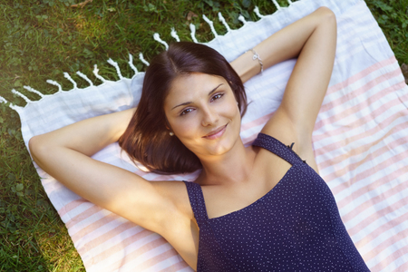 Pretty young woman relaxing on the grass lying on her back on a rug with her hands behind her head smiling up at the camera