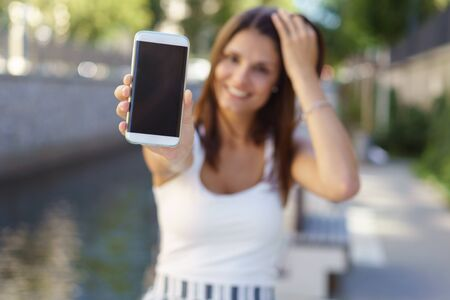 alongside: Young woman holding out her blank smartphone with the screen towards the camera as she stands alongside a river or canal in summer clothes, focus to the phone