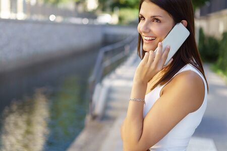 Happy young woman chatting on her mobile outdoors as she stands alongside a canal or river looking up with a smile as she listens to the conversation Stock Photo