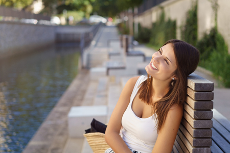 alongside: Happy young woman sitting alongside a river daydreaming or reminiscing looking up into the air with a blissful smile