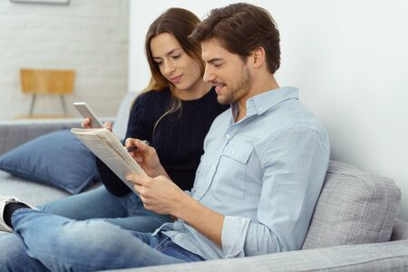 couple on couch: Young couple checking the commercial classified advertisements in a newspaper together with the wife dialling a number on her mobile phone