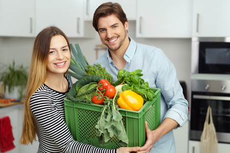 domicile: Happy healthy young couple with fresh vegetables in a green plastic box in their arms standing grinning at the camera in their kitchen