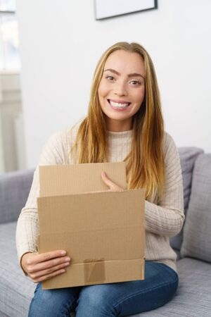 delivery room: Cute young blond woman with a lovely beaming smile sitting on a sofa with an opened brown cardboard box on her lap looking at the camera