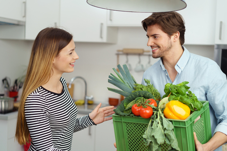 Young man bringing home a plastic box filled with fresh vegetables to cook to be greeted in the kitchen by his smiling wife