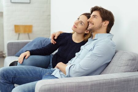 they are watching: Happy young couple sitting daydreaming or watching something above their heads as they relax arm in arm on the sofa Stock Photo