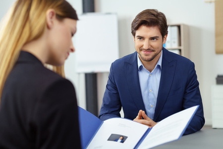 Handsome young businessman in a job interview smiling as he watches a female business executive reading his CV in a file