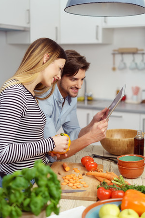 Young couple preparing a meal together in the kitchen with fresh fruit and vegetables pausing to look at something on a tablet computer Stock Photo
