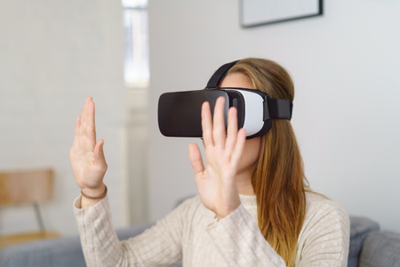 Young woman in 3D glasses virtual reality VR headset groping virtual wall with her open palms in front of her Stock Photo