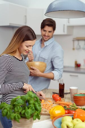 diet dinner: Happy young couple preparing dinner together in the kitchen with an assortment of fresh fruit and vegetables in a healthy diet concept