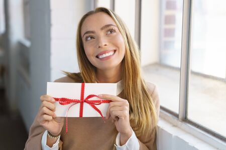 Young woman with a Valentines gift in an envelope tied with red ribbon held in her hands looking up with a happy dreamy smile as she thinks of her sweetheart Stock Photo