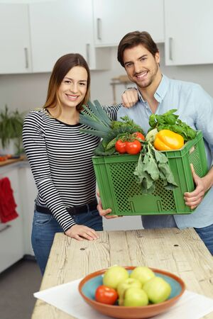 domiciles: Happy healthy couple bringing in fresh produce into the kitchen in a plastic crate to prepare the evening meal