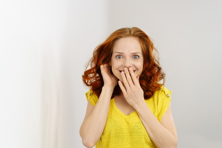 Surprised happy young woman covering her mouth with her hand as she grins at the camera with a wide eyed startled expression