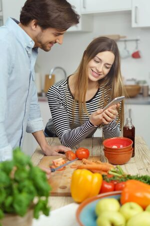 Young couple checking a text message on a mobile phone while preparing a healthy meal together with fresh vegetables Stock Photo
