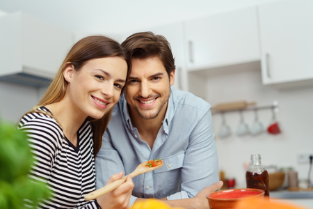 Happy smiling couple cooking a meal together in their kitchen posing side by side for the camera with their heads close