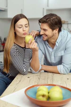 they are watching: Healthy young woman kissing a green apple watching by her grinning amused husband as they sit in the kitchen Stock Photo