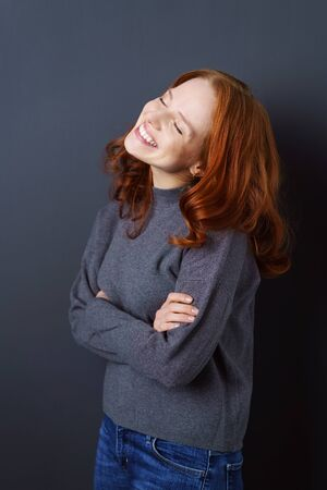 blissfully: Smiling blissfully happy young redhead woman standing with folded arms, head tilted back, eyes closed and an ecstatic smile