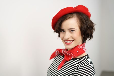 Stylish smiling friendly young woman wearing a red scarf and beret looking sideways at the camera with a vivacious grin, with copy space alongside on a wall
