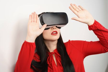 Young woman reacting to her simulated environment on a virtual reality headset holding her hands up in front of her in a defensive gesture