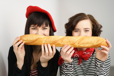 Two laughing vivacious young women holding a long French baguette in front of their faces as they grin at the camera