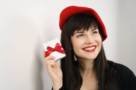 beaming: Romantic young woman in a sexy red French beret holding a Valentines, Christmas or anniversary gift box with decorative ribbon as she looks up with a beaming smile of pleasure