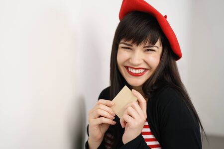 beaming: Happy excited stylish woman in a red French beret holding a bank credit card with a beaming smile of anticipation at her shopping opportunities