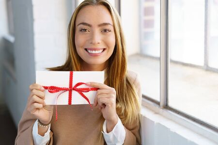Happy young woman holding up a gift or award in a white envelope tied with a red ribbon looking at the camera with a beaming smile