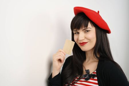 Pretty fashionable young woman in a French beret and matching red scarf holding a credit card with a smile of anticipation as she contemplates her shopping opportunities