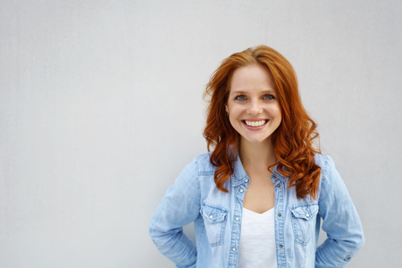 Friendly attractive young redhead student in a casual faded denim top standing against a white wall with copy space smiling at the camera Stockfoto