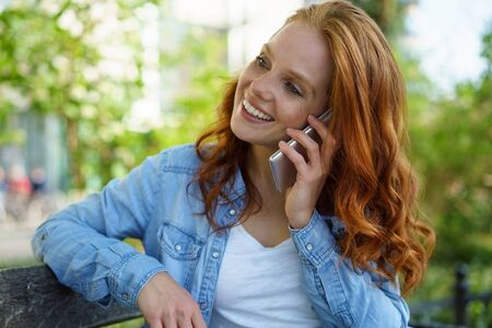 redhaired: Gorgeous young redhead woman chatting on a mobile phone as she relaxes on a bench in a leafy green street in town