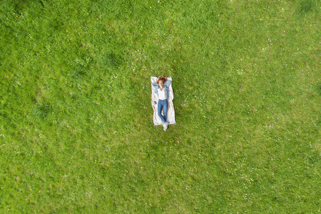 Young woman relaxing on a rug on the grass viewed from high overhead as a diminutive person in the center of a field of green grass Stock Photo