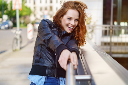 Vivacious lively attractive young woman with long curly coppery red hair holding onto a bridge railing in an urban street laughing at the camera Stock Photo
