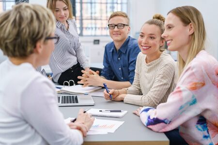 study group: Group of motivated young business people or students sitting grouped around a table having a discussion smiling as they listen to a woman with her back to the camera