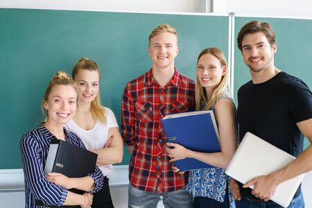 study group: Group of male and female university friends posing in front of a clean chalkboard in the classroom holding class notes and smiling at the camera
