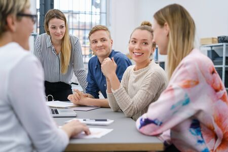 study group: Young business team having a meeting grouped around a table with focus to a smiling young woman listening to a colleague
