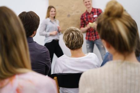 Joven escuchando una presentación de negocios o una conferencia en la universidad con un grupo de colegas visto desde la parte trasera con enfoque a la parte posterior de su cabeza Foto de archivo - 78571919