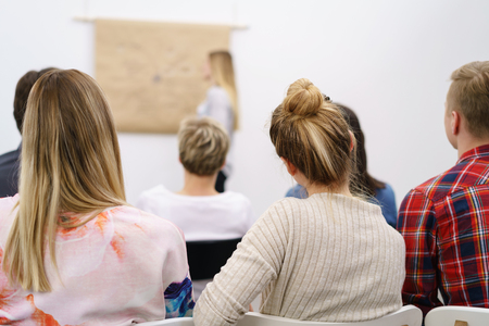 Young businesspeople or students in class listening to a presentation or lecture viewed from behind