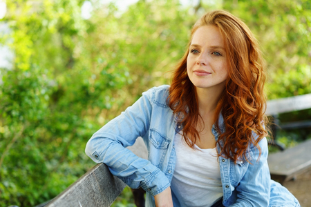Thoughtful young redhead woman sitting on a bench in the park against a backdrop of greenery staring off into the distance with a faraway expression