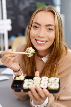 Smiling young woman enjoying a takeaway sushi at her desk at the office holding a mouthful ready to eat on chopsticks Stock Photo