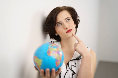 Thoughtful young woman deciding on her holiday destination holding a world globe in her hand as she looks pensively up into the air with her finger to her chin Stock Photo